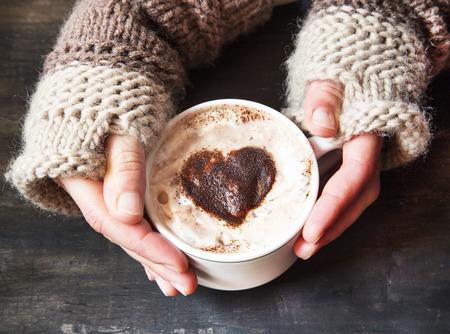 capuchino: Manos que sostienen Cappuccino caliente con espuma y cacao en forma de corazón