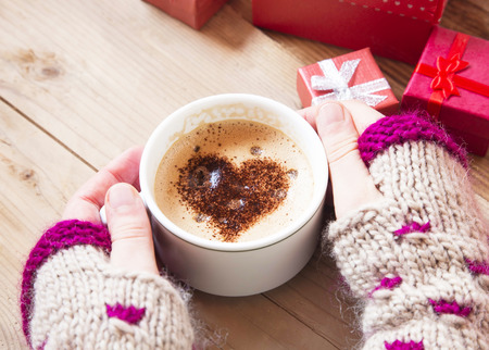 morning breakfast: Hands Holding Warm Cappuccino with Froth and Cocoa Heart Shape Stock Photo