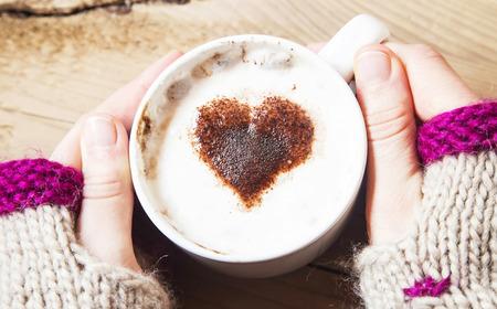 나무 배경에 심장 모양 카푸치노 커피 잔을 들고 손