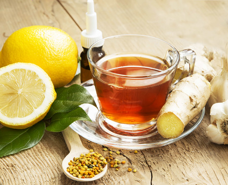 cold remedy: Fresh Lemon Tea in Transparent Cup with Ginger,Pollen and Garlic on Wooden Background.Natural Cold Remedy