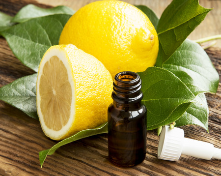 Lemon Essential Oil Bottle with Lemon Fruit and Leaves on Wooden Background