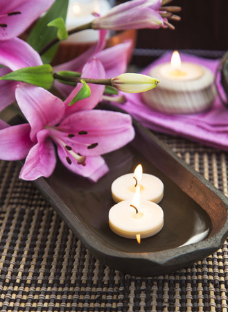 Spa Lilies and Floating Burning Candles in a Wooden Water Bowl, Beautiful Calm Setting photo