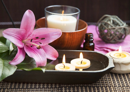 Spa Scene with Pink Lilies and Wooden Water Bowl, Burning Candles and Bamboo Background photo