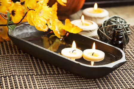Spa with Floating Burning Candles in a Wooden Water Bowl, Beautiful Calm Setting photo