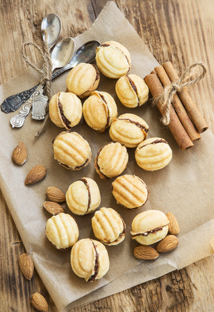 Walnuts Shape Cookies with Chocolate Filling, Sweet Homemade Cookies with Almonds and Cinnamon Sticks photo