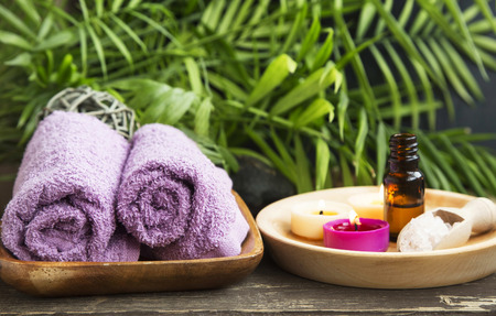 wellness: Spa.Scented Candles, Essential Oil Bottle and Cotton Towels on Green Wellness Background