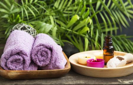 Spa.Scented kaarsen, etherische olie fles en katoenen handdoeken op Green Wellness Achtergrond