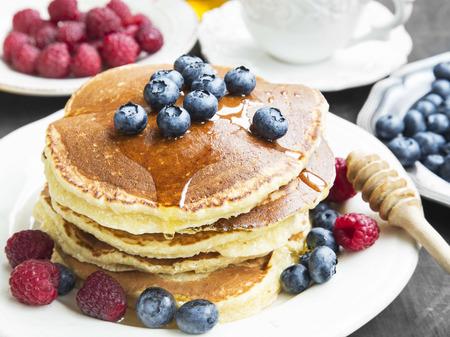 petit dejeuner: Petit d�jeuner avec cr�pes au miel et framboises, bleuets petit-d�jeuner sucr� Banque d'images