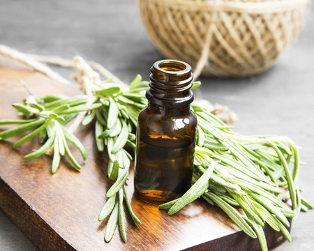 Rosemary Herb Essential Oil Bottle on Wooden Board with Rosemary Herb Bunch