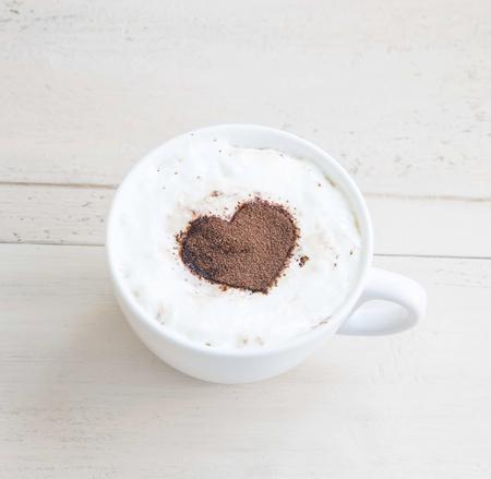 taza cafe: Caf� con leche taza de caf� con cacao en forma de coraz�n en el fondo de madera