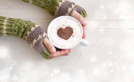 매직 겨울 배경에 코코아 모양 아늑한 양모 손을 따뜻하게 커피 라떼 잔을 들고