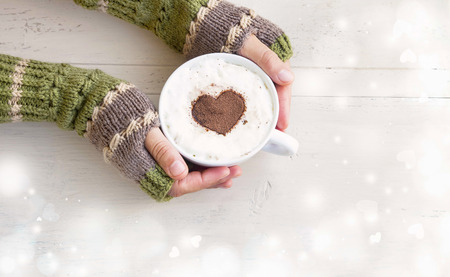 and in winter: Holding Coffee Latte Cup with Cocoa Shape and Cozy Wool Hands Warmers on Magic Winter Background Stock Photo