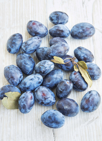 organic plants: Ripe Autumn Plums Fruits on Wooden Background