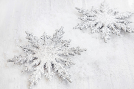 flocon de neige: Two Silver Glittered Christmas Snowflakes Ornaments in the Snow Banque d'images