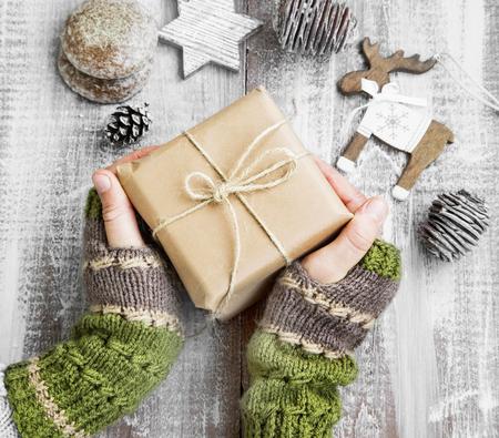 Vrouwelijke handen met kerstcadeau Vintage verpakt op geverfd hout met ornamenten en handwarmers Stockfoto