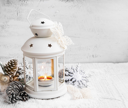 white winter: White Christmas Lantern with Burning Candle in the Snow on Painted Wood