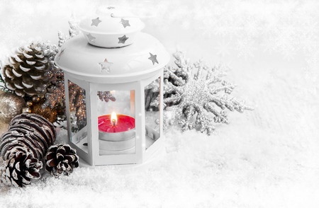 White Christmas Lantern with Burning Candle in the Snow and Ice Snowflakes Stock Photo