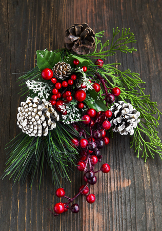 decoration: Christmas Decoration with Fir Tree, Red Berries Branches and Cones on Wooden Background