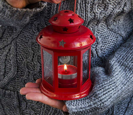 black hands: Female Hands Holding Red Christmas Lantern with Burning Candle