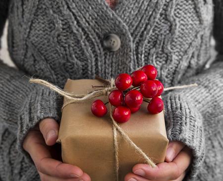 빨간 딸기의 무리와 여성을 들고 소박한 장식 된 크리스마스 선물