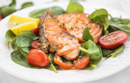 salad in plate: Salm�n con especias a la plancha con ensalada de espinaca y tomates y rodajas de lim�n