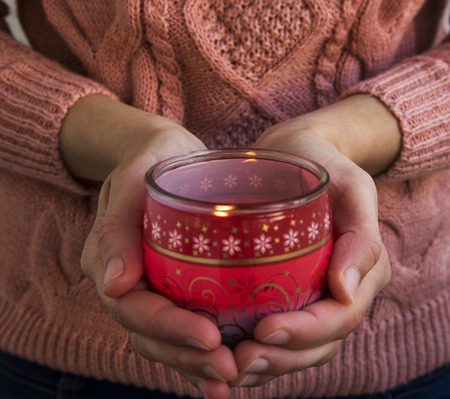 christmas scent: Female Hands Holding Christmas Scent Burning Candle