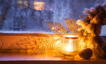 Christmas Window Lantern with Decoration on Frozen Winter Window