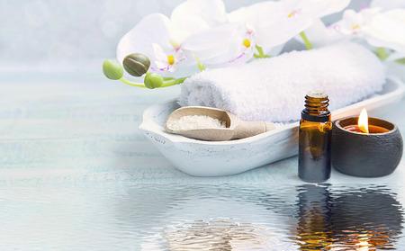 Spa bodegón con una toalla, orquídea blanca, sal marina, aceite de baño y una vela en la reflexión del agua