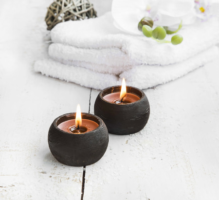 towel: Spa still life with burning candle, white towels and orchid Stock Photo