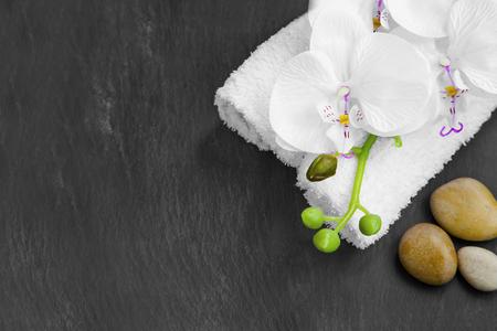 Spa Stilleven met massage stenen, witte orchidee en handdoeken op een grijze achtergrond