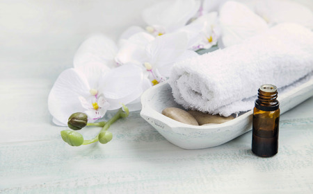 Spa still life with white orchid and towel, bath essence oil bottle