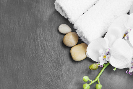 relaxation background: Spa still life with massage stones,white orchid and towels on grey background