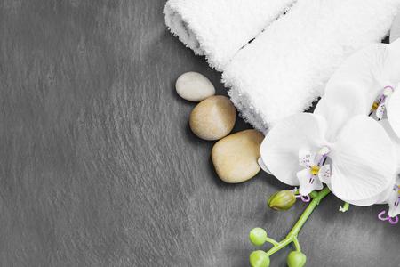 Spa Stilleben mit Massagesteine, weiße Orchidee und Handtücher auf grauem Hintergrund Standard-Bild - 52244658