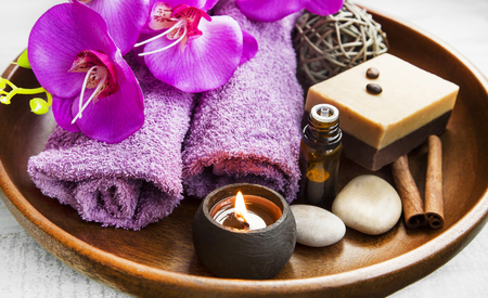 Spa products in wooden tray with towels,scent candle,orchid, bath oil