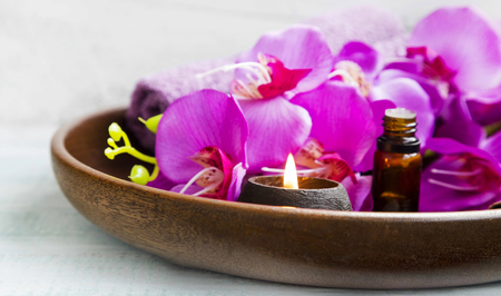 brown background: Spa products in wooden tray with towels,scent candle,orchid, bath oil