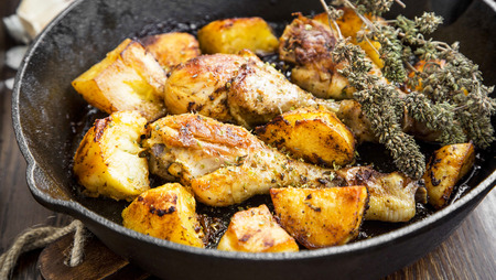 vegetable background: Roasted chicken legs with baked potatoes garnish and herbs in a cooking pan Stock Photo