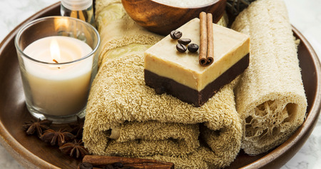 brown background: Spa setting with coffee and cinnamon soap, towel candle and sea salt