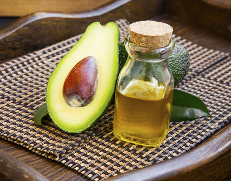 medical care: Avocado oil bottle with avocado fruit on wooden background