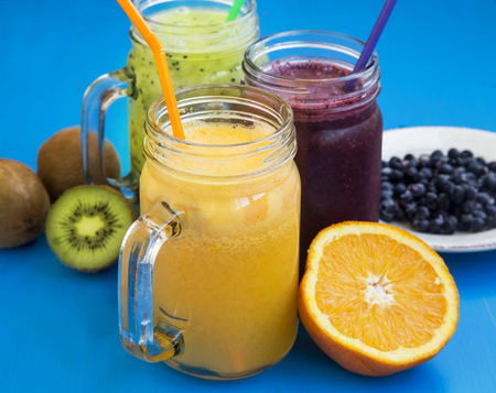 background colors: Healthy fruit juices with green kiwi,blueberries and orange