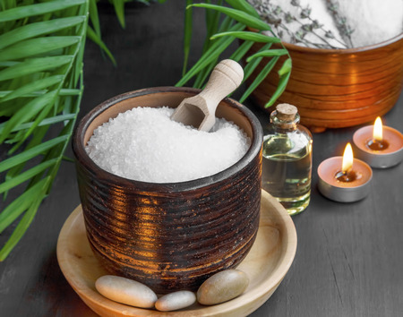 beauty background: Spa setting with bath salt and oil, massage stones and burning candles