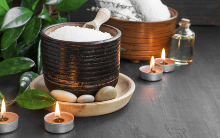 salon background: Spa setting with bath salt and oil, massage stones and burning candles
