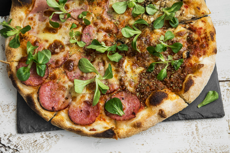 cornsalad: Pizza salami and ham with cheese and cornsalad leaves , rustic fresh baked italian pizza