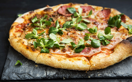 cornsalad: Pizza salami and ham with cheese and cornsalad leaves , rustich fresh baked italian pizza