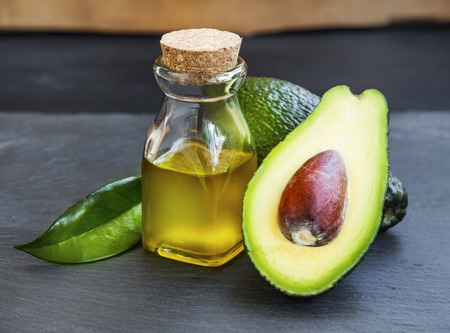 green background: Avocado oil bottle with avocado fruit on wooden background