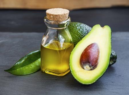 Avocado-olie fles met avocado fruit op houten achtergrond