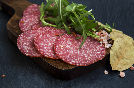 salami slices: Salami slices on wooden board with spices and arugula