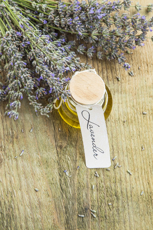 lavender oil: Lavender oil with lavender flowers and label on rustic background