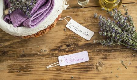 Lavendel Welness Spa Stilleben mit Etiketten, Kerze, Körperöl, Lavendelblüten und Handtücher