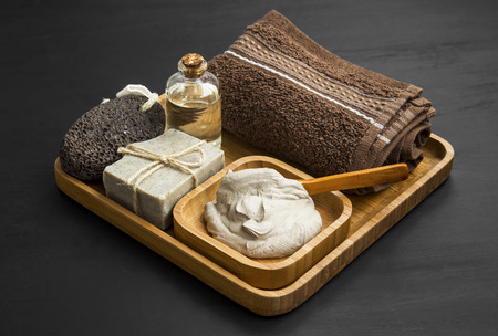 Skincare spa with clay mask,natural soap,soft towel and face oil in wooden bamboo tray Imagens