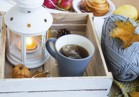 tea cosy: Cosy autumn decor with cup of tea, lantern, knitting wool , dried leaves and lights